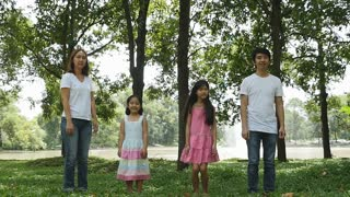 Asian family jumping together in the park