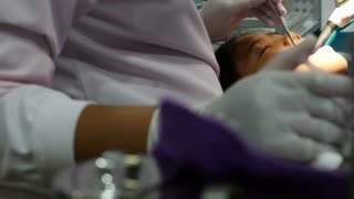 Asian girl at the dentist has tooth treated, Pan shot