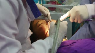 Asian girl at the dentist has tooth treated