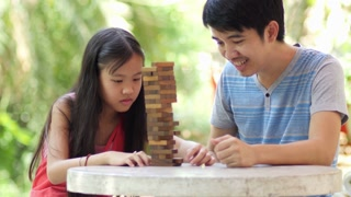 Asian girl playing a game of risk trying to move wooden blocks with her father
