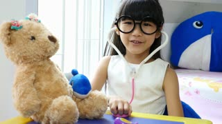 Asian girl playing doctor with doll