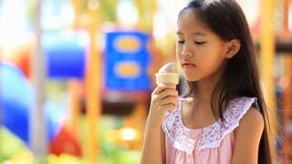 Asian kid enjoy with icecream at playground