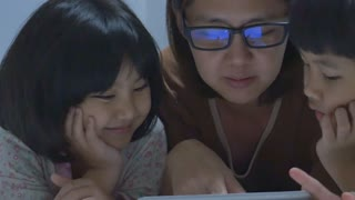 Asian mom lies with her daughters and plays with digital tablet together, Pan shot