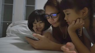 Asian mom lies with her daughters and plays with digital tablet together, Zoom shot