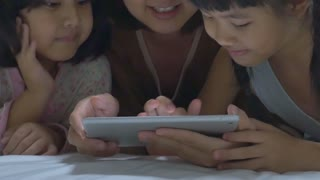 Asian mom lies with her daughters and plays with digital tablet together