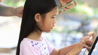 Asian mother braids her daughter's hair