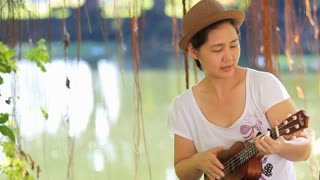 Asian mother playing ukulele with her daughter in park