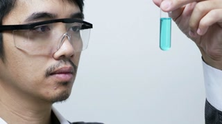 Asian scientist in lab working on chemicals analysis.