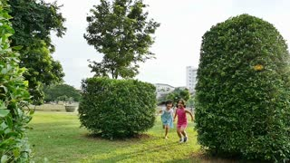 Asian sisters running around in the park and laughing together, Slow motion shot