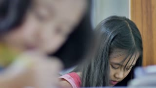 Asian student doing exam in classroom, Rack focus