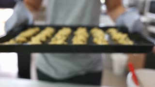 Asian woman holding cookies tray, Zoom in shot