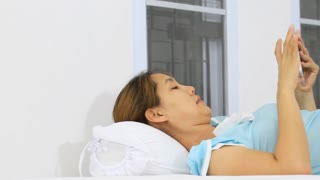 Asian woman laying on the bed and using tablet computer