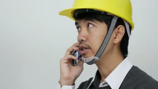 Asian young engineer talking with smart phone on white background