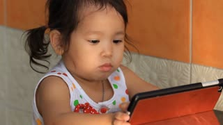 Baby Asian girl playing tablet PC