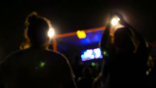 Blurred silhouettes of concert crowd in front of bright stage lights in Asia, Slow motion shot