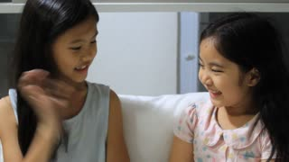 Children having fun, little Asian girls playing together on the bed