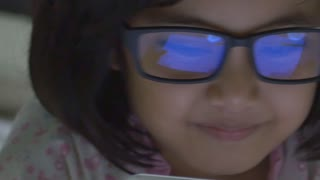 Close up of Asian child using tablet computer with reflection in glasses, Pan shot