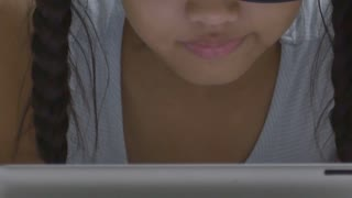 Close up of Asian child using tablet computer with reflection in glasses, Tipt up shot