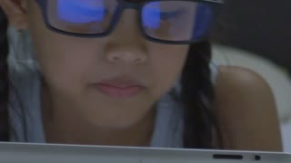 Close up of Asian child using tablet computer with reflection in glasses