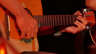Close up of Asian musician is playing on guitar in concert