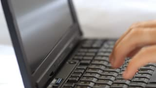 Close up of hand writing laptop keyboard on the bed