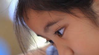 Close up of little Asian girl painting a picture on the table, Tilt down shot