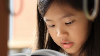 Close up of little Asian girl reading a book in library
