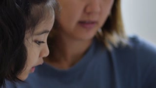 Close up of little Asian girl with mother doing homework