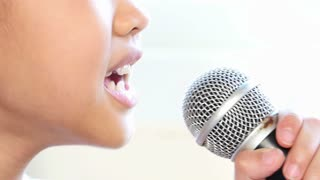 Closeup shot of a cute little Asian girl singing