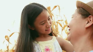 Hand held of Asian girl with her mother enjoying in the meadow together, Slow motion shot