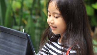 Happy asian child playing with tablet