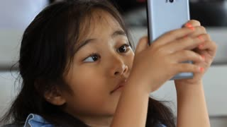 Happy Asian child talking and touching with smart phone