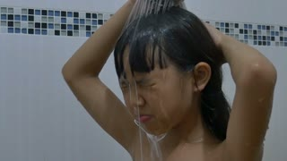 Happy Asian child washes hair in bathroom