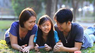 Happy Asian family playing game in smart phone together in park