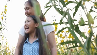 Happy Asian girl and mother play in the meadow, Slow motion shot