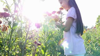 Happy Asian girl holding the flower in the field with sunlight, Slow motion shot
