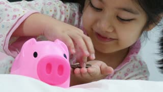 Happy Asian girl saving money in piggy bank
