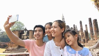Happy Asian family travel. Family on vacation takes a photo together with a smart phone
