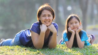 Happy Asian mother and daughter on grass at sunny summer day in park