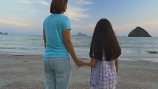 Happy Asian mother and daughter on vacation at the beach, slow motion