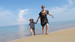 Happy Asian mother and daughter running on the sand beach together, Phuket Thailand