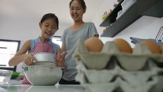 Happy Asian mother baking cookie with little daughter in apron, Pan shot