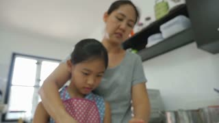Happy Asian mother baking cookie with little daughter in apron, Tilt down shot