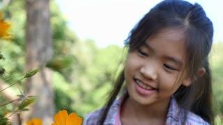 Happy little Asian girl looking flower in the garden, Slow motion shot