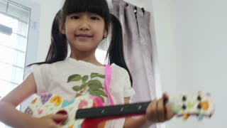 Laughing little Asian girl playing her guitar788-Music.mov