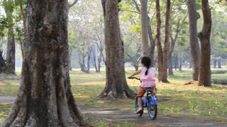 Little Asian child cycling together in historical park