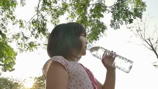 Little Asian Child drinking water in the park, Slow motion