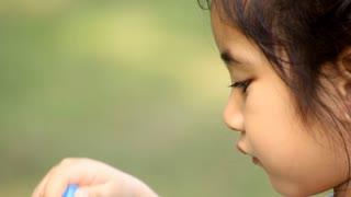 Little Asian child having fun making bubbles