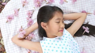 Little Asian child laying down on the floor with falling flowers, Slow motion shot