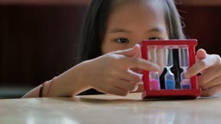 Little Asian child looking at hourglass in class